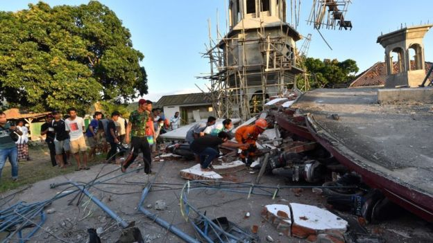 Residents and Indonesian search and rescue personnel look under the ruins of a mosque in Pemenang