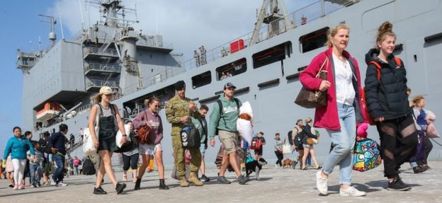 Evacuees leave HMAS Choules at the port of Hastings, Victoria