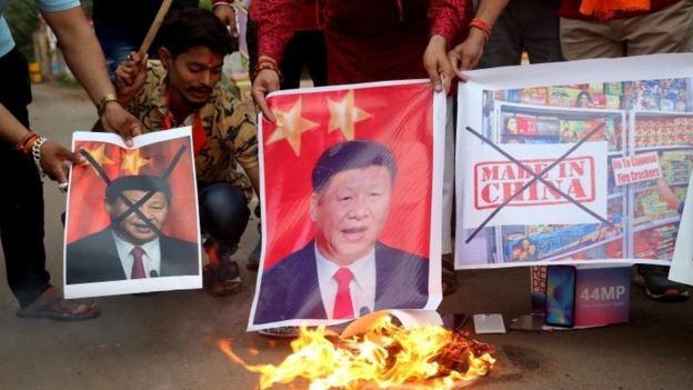 Activists shout slogans as they stage a protest against China, burning posters of Chinese President Xi Jinping, in Bhopal, India
