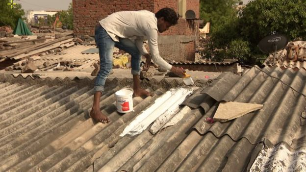 Painting roofs with white reflective paint helps reduce the heat