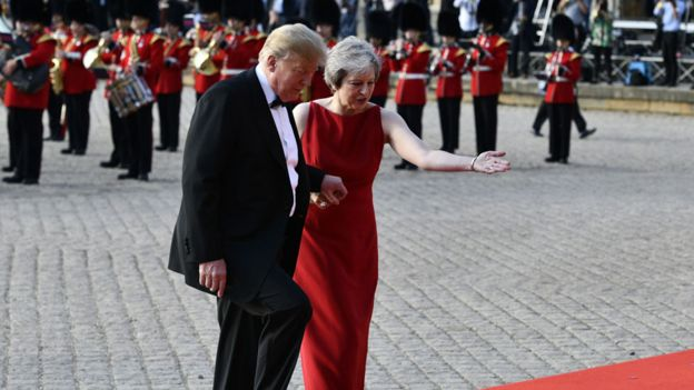 Donald Trump segura a mão de Theresa May para subir escadas