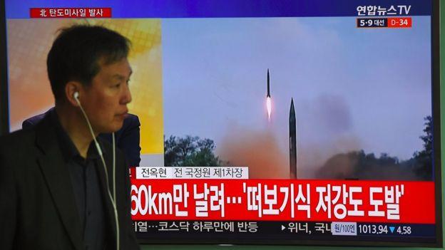 韩国首尔火车站内一名市民走过正在播报朝鲜试射导弹消息的电视屏幕(5/4/2015)