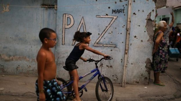 Crianças passam em frente a muro cravejado de balas