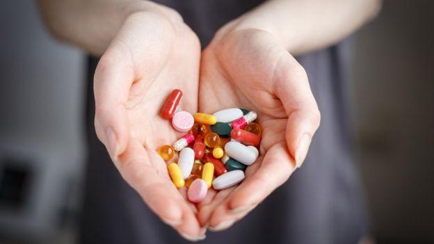 Manos de mujer mostrando pastillas.