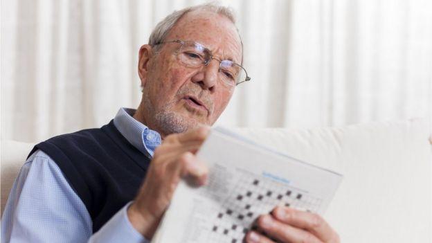 Older man tackling a crossword puzzle