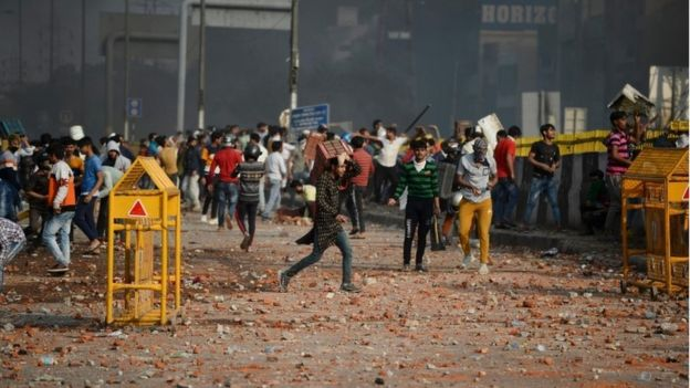 Demonstrators gather along a road scattered with stones following clashes between supporters and opponents of a new citizenship law, at Bhajanpura area of New Delhi on February 24, 2020