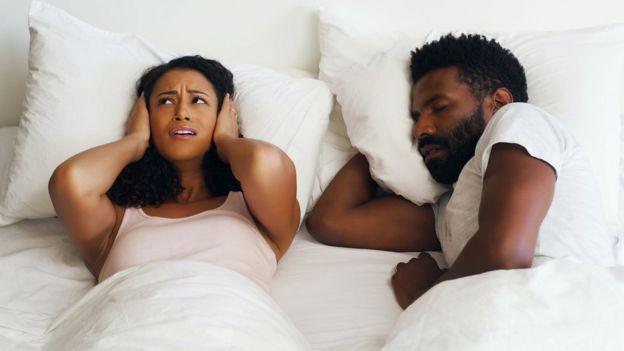 Mulher tampa os ouvidos enquanto seu marido ronca