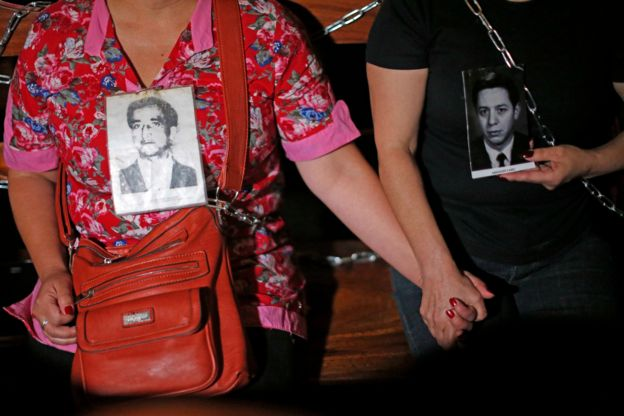 Relatives of some of the victims of Pinochet's regime hold hands while chained to church pews on 22 December