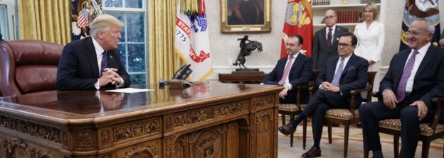 US President Donald J. Trump (L), hosting the Mexican delegation, talks with Mexican President Enrique Pena a Nieto on the phone to announce a trade deal in the Oval Office of the White House