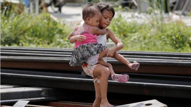 Menina filipina carregando bebê entre as barreiras de metal que protegem dique de rio