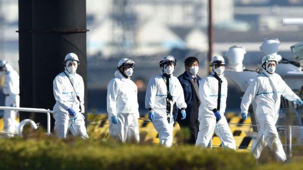 """Parte del personal vestido con equipo de protección encargado de atender a los pacientes sospechosos a bordo del crucero """"Diamond Princess""""."""