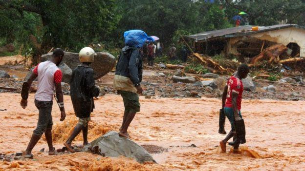 Afectados caminan entre la inundación.