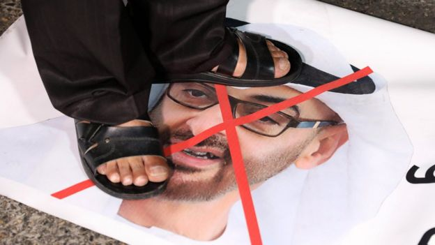 A Palestinian protester stands on a photo of Abu Dhabi Crown Prince Mohammed bin Zayed at a protest in Bethlehem against the UAE's decision to normalise relations with Israel (16 August 2020)