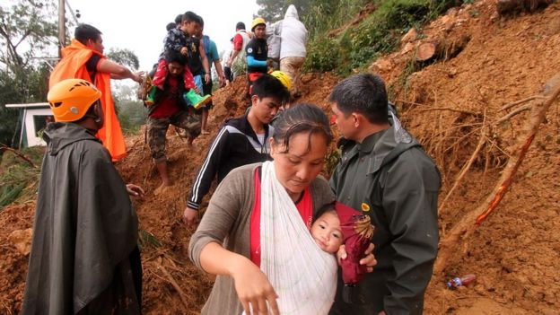 People carrying children climb over muddy landslides in Itogon