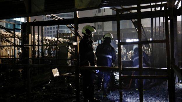 Firemen inspect the debris after the fire