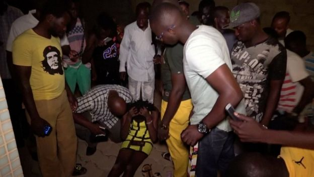 A wounded restaurant customer sits on the ground following an attack by gunmen on a restaurant in Ouagadougou, Burkina Faso