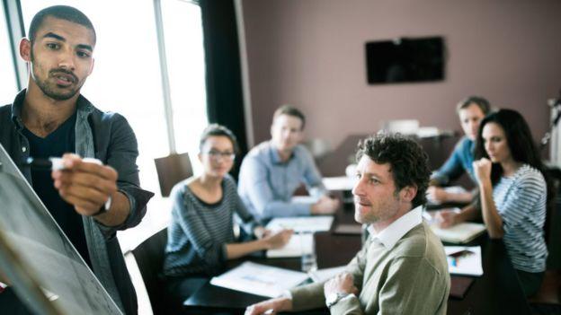 Un hombre da una presentación ante sus colegas en una junta de reuniones.