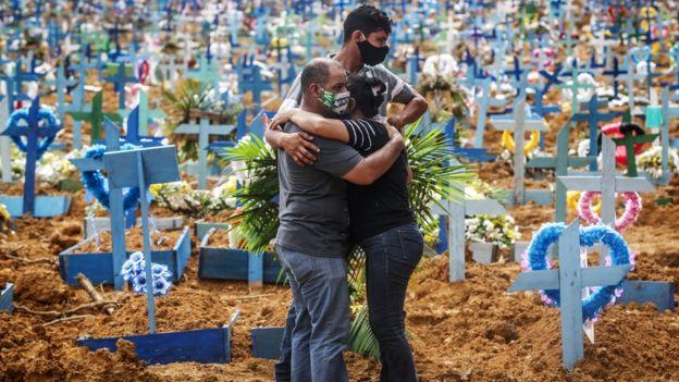Deudos de víctimas del covid-19 en un cementerio en Manaos, Brasil.
