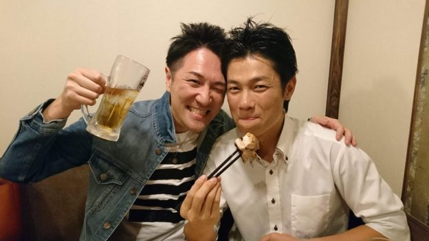 Yuichi Ishii toasting with beer in the company of a friend