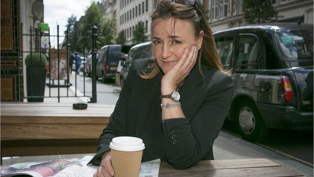 Manuela sits with a takeaway coffee