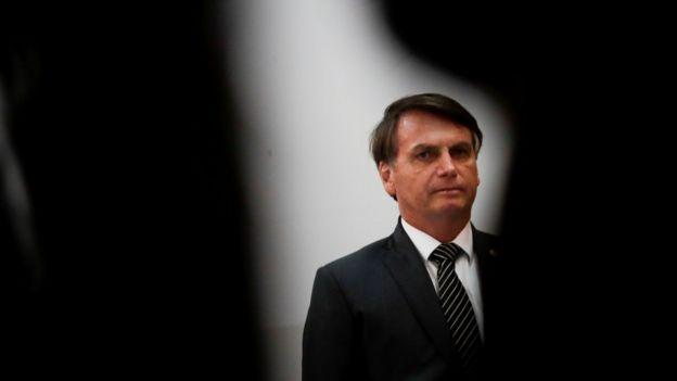 O presidente Jair Bolsonaro aparece de pé, olhando para frente