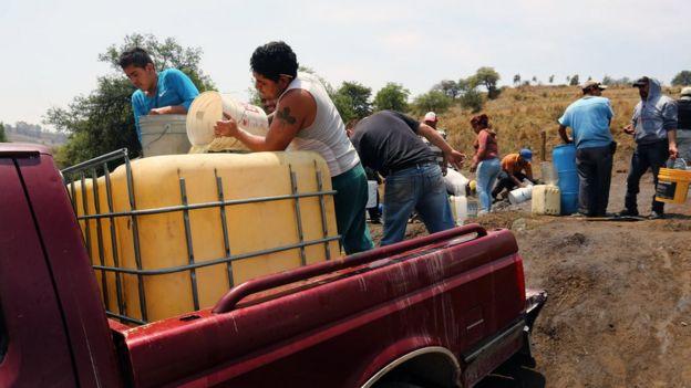 Pobladores abasteciéndose de combustible a partir de un oleoducto de Pemex.