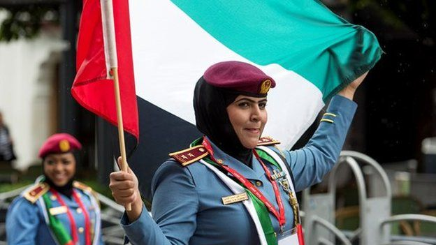 Police officer waves a flag while on parade in Cardiff