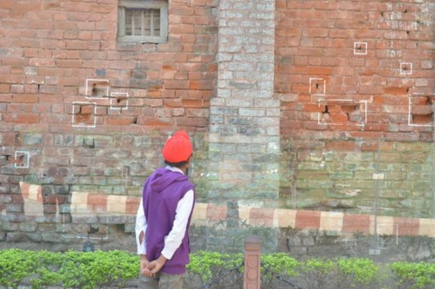 A visitor looking at the bullet marks on a wall on the eve of 95th anniversary of the massacre at Jallianwala Bagh on 12 April 2014 in Amritsar.