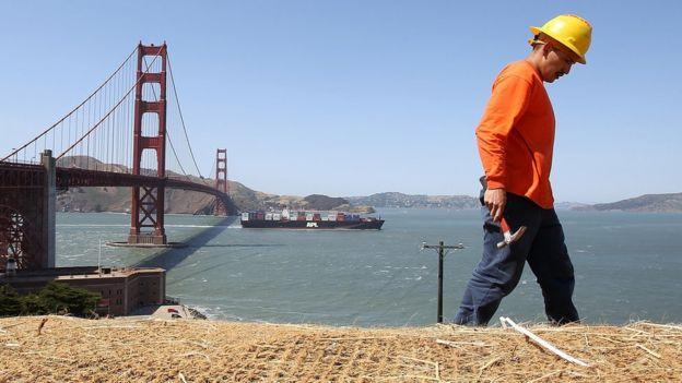 Trabalhador com a ponte Golden Gate, em São Francisco, ao fundo