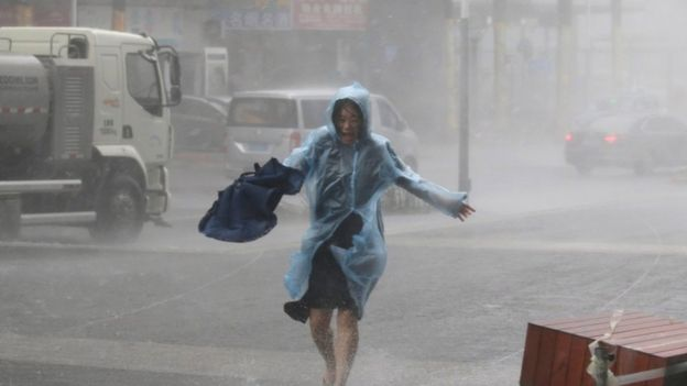 A woman runs in a waterproof with an umbrella in hand in heavy rainstorm in Shenzhen
