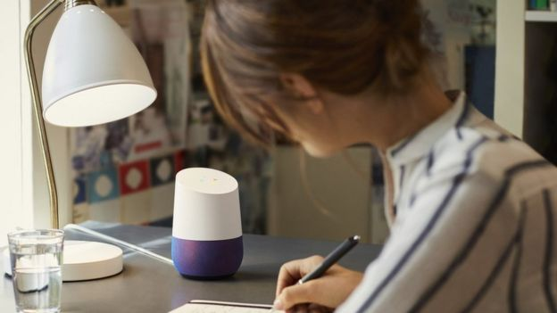 Woman with Google Home speaker on desk