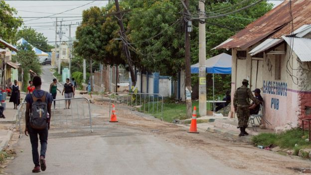 Police and soldiers man a checkpoint in Denham Town