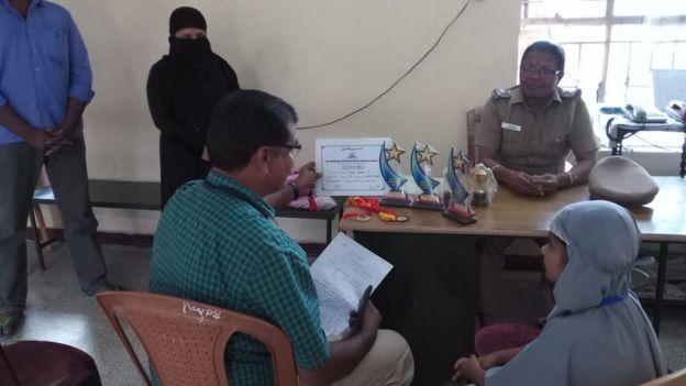 A polícia alertou autoridades locais sobre a reclamação de Hanifa - na imagem, a policial, Hanifa e uma autoridade local; na mesa, os prêmios e certificados escolares da menina