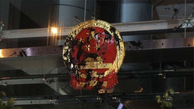 照片显示示威者向中国国徽投掷墨水弹,国徽被涂污半黑。