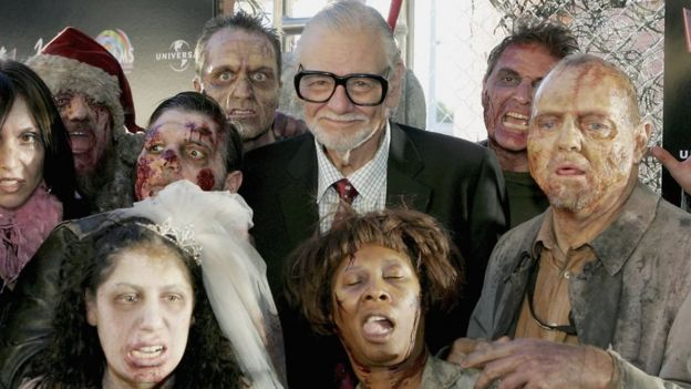 Director George A. Romero is surrounded by actors portraying zombies as he arrives for the world premiere of his movie 'Land of the Dead' in 2005