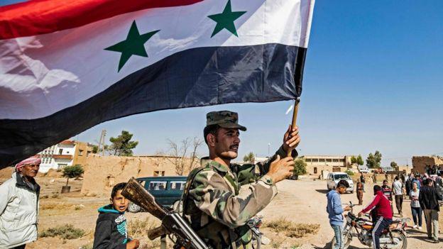 Солдат правительственных войск Сирии с государственным флагом