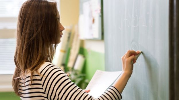Woman at the blackboard doing accounts.