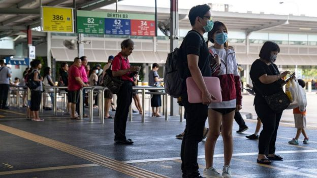 Pessoas em estação de transporte público usando máscaras faciais