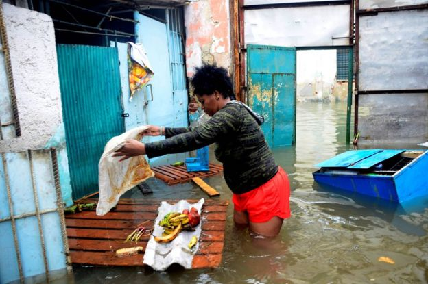 A woman tries to rescue some food from her flooded house in downtown Havana, Cuba, 10 September