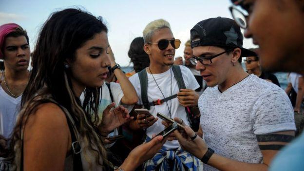 Jóvenes miran sus teléfonos en el Malecón de La Habana.