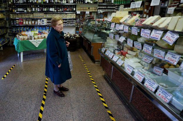 زنی در مغازه خواربار فروشی در رم. خطوط زرد روی زمین برای آن است تا مشتریان فاصله خود را با هم حفظ کنند