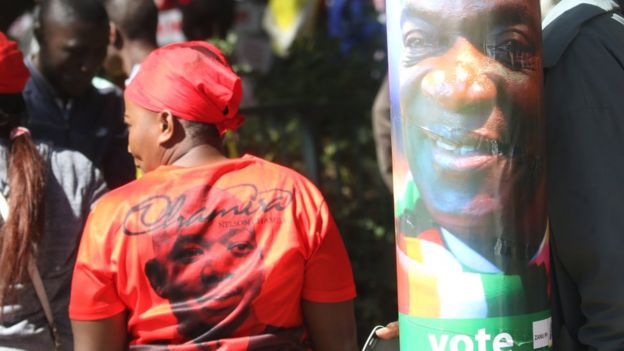 An MDC supporter (L) by a poster of Zanu-PF candidate Emmerson Mnangagwa in Harare, Zimbabwe