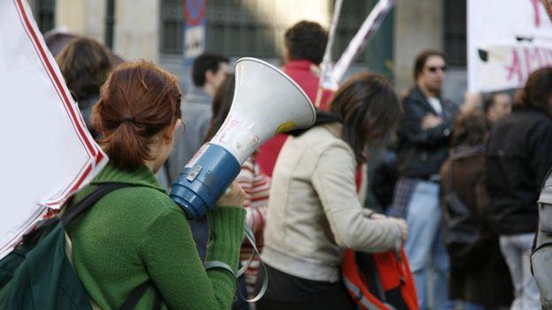 Diversos estudantes aparecem em rua com cartazes, uma delas segurando um megafone
