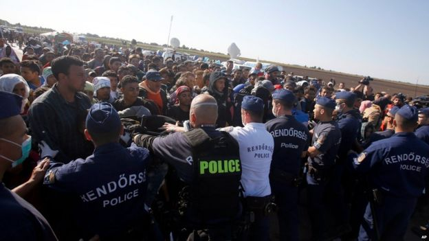 Police try to prevent migrants in Roszke, southern Hungary, leaving a makeshift camp for asylum seekers on Wednesday - many later broke through the police lines
