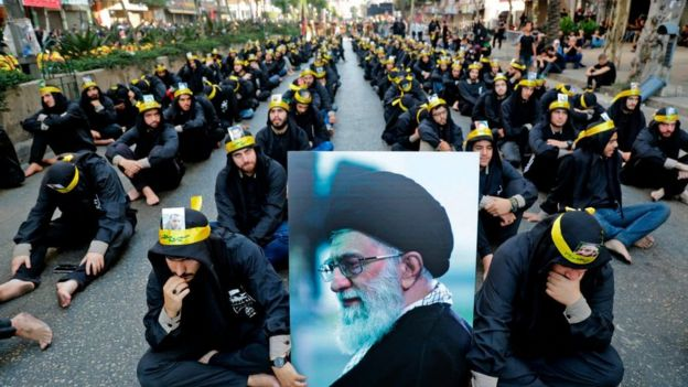 Supporters of the Lebanese Shia Hezbollah movement hold a picture of Iran's Supreme Leader Ayatollah Ali Khamenei as they take part in a religious mourning procession in Beirut, on September 10, 2019