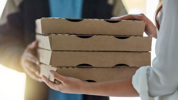 Hombre entrega cajas de pizza