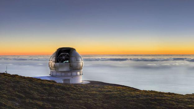 Gran Telescopio Canaria sobre un horizonte de nubes iluminadas por el Sol