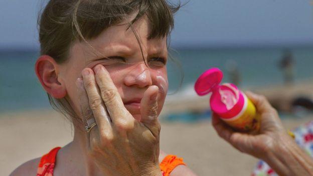 Mujer aplicando crema solar a una niña.