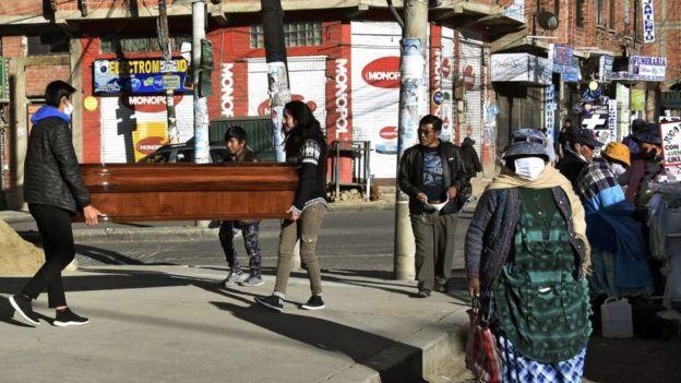 Dos personas cargando un ataúd en El Alto.