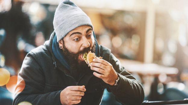 Hombre come una hamburguesa.